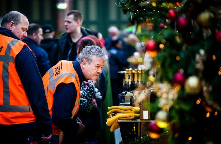 Medewerkers van HTM in Den Haag zoeken op een kerstmarkt in het Openbaar Vervoer Museum hun eigen kerstpakket bij elkaar.  Beeld Freek van den Bergh