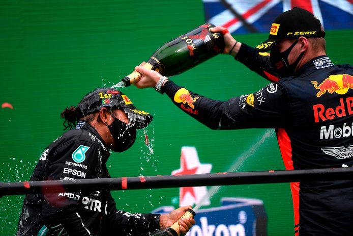 Max Verstappen giet de champagne uit boven het hoofd van Lewis Hamilton.