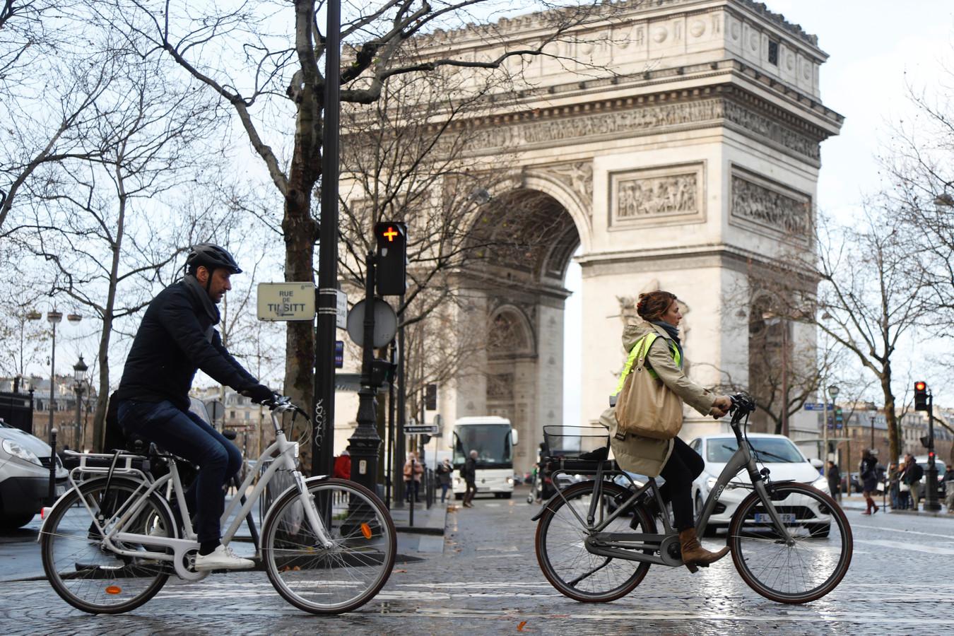 Mensen passeren tijdens het spitsuur per fiets de Arc de Triomphe in Parijs, waar alle transportvakbonden al meer dan een week in staking zijn.