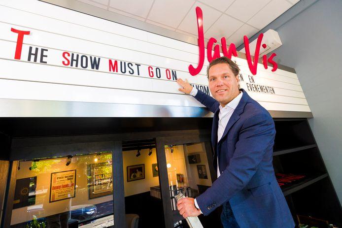 Jan Dirk Vis plakt letters op een bord bij de ingang van zijn bedrijf.