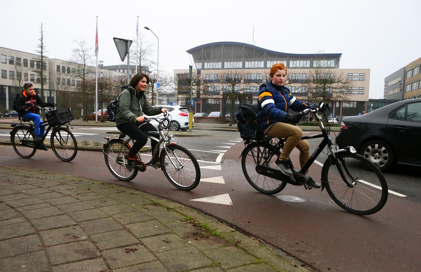 Fietsers op de rotonde voor het stadhuis. Ook hier delen ze de weg met auto's.