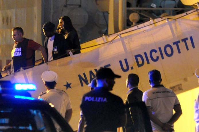 Een migrant wordt onder politiebegeleiding van boord gehaald.