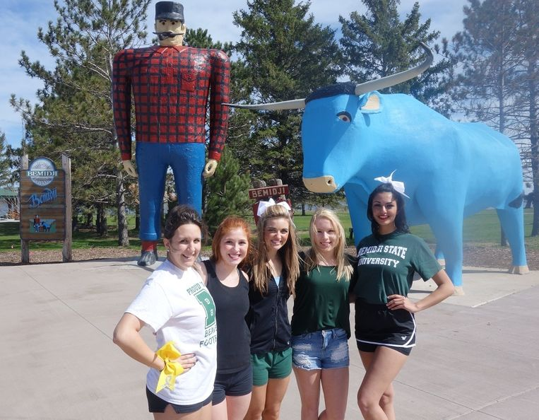 De dames cheerleaders bij het standbeeld van Bunyan. Uiterst links Baily Anderson, in het midden Alisha Houdek. Beeld Erik van Zwam
