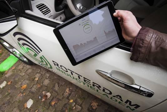 Een elektrische auto wordt opgeladen boven een laadplaat met behulp van een app.