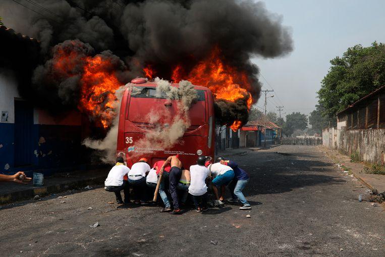 Demonstranten duwen een in brand gestoken bus in Ureña. Beeld AP