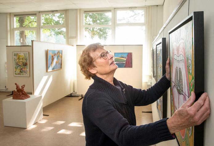 Atty Heijting hangt schilderijen op voor de eerste expositie van de Kunstkelder Putten op een tijdelijke nieuwe locatie in de school Veenhuizerveld, waar de Kunstkelder minstens tot september 2019 zit.