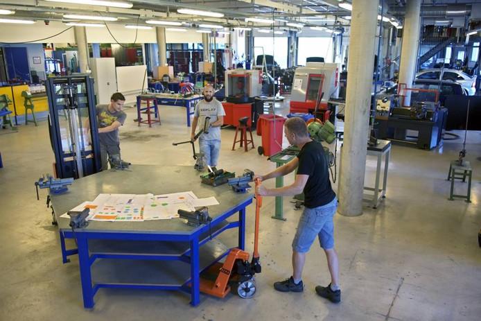 Van links naar rechts: Erwin Heuvelmans, René Hollemans en Marijn Elich zetten de meubels weer op hun plaats in het vaklokaal. Op tafel ligt een plattegrond met de indeling van de ruimte. foto Johan Wouters/pix4profs