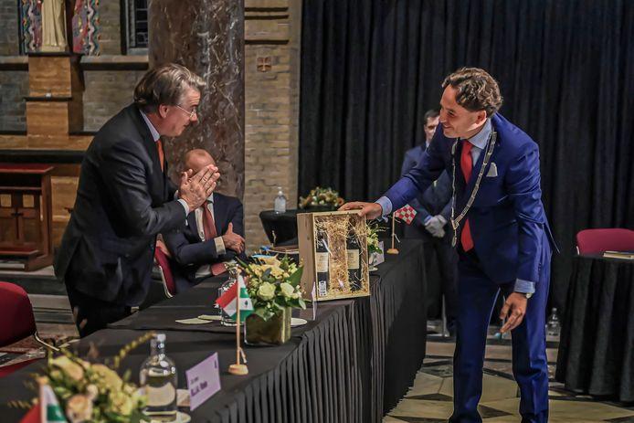 Kersverse burgemeester Bernd Roks van Halderberge overhandigt een doosje 'Spaandonk-wijn' aan scheidend Commissaris van de Koning Wim van de Donk.