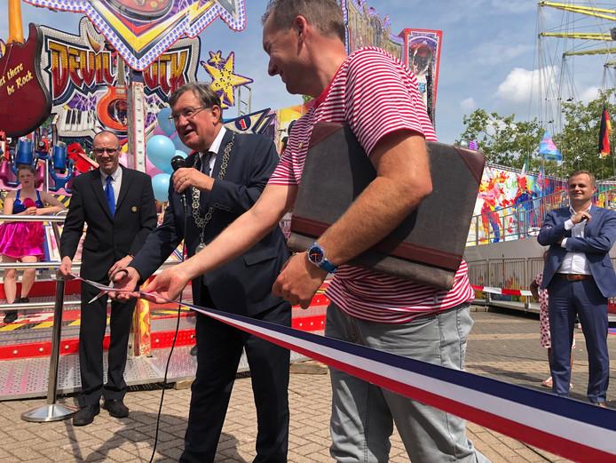 Kermismeester Pascal Donkers (voorgrond) kijkt toe hoe burgemeester Hellegers het lint doorknipt. De kermis Uden is van start. Op de achtergrond kijkt kermiswethouder Gijs van Heeswijk toe.