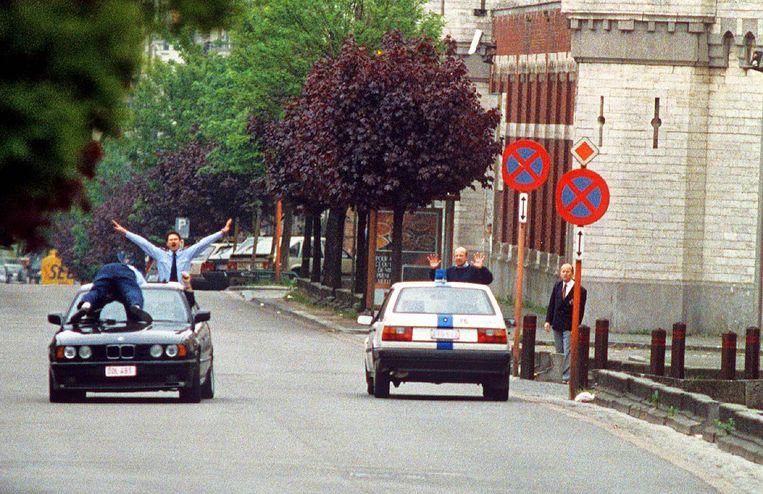Het iconische beeld: een gevangenismedewerker ligt tijdens de vlucht op de motorkap. De drie gijzelnemers krijgen een vrijgeleide in hun BMW.