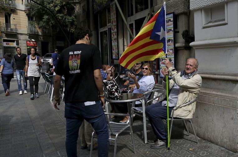 Een man houdt op een terras de Catalaanse vlag vast. Beeld reuters