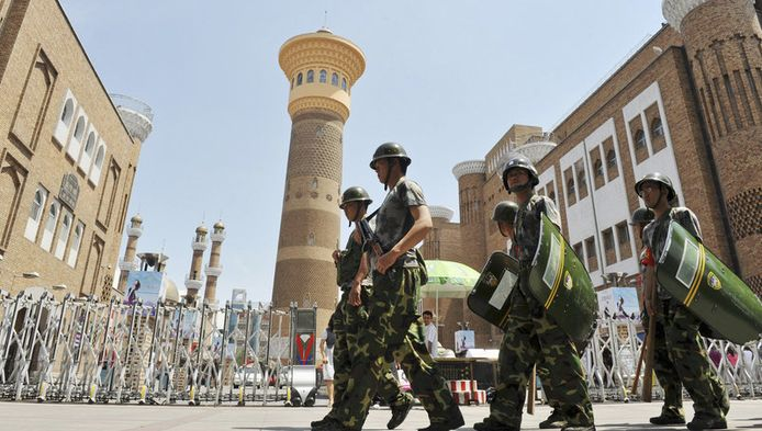 Chinese veiligheidstroepen patrouilleren in de straten van Urumqi, een jaar na de dodelijke rellen.