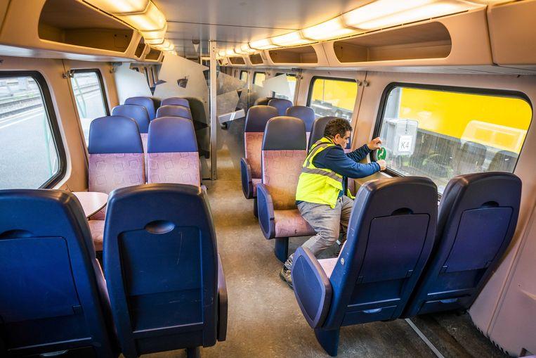 Een monteur van de NS plakt stickers in een trein, die aangeven op welke stoelen wel of niet mag worden gezeten.  Beeld ANP