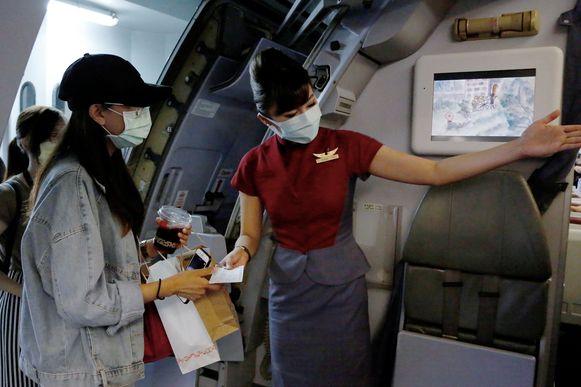 Een airhostess wijst een van de 'reizigsters' haar plaats aan op de nepvlucht.