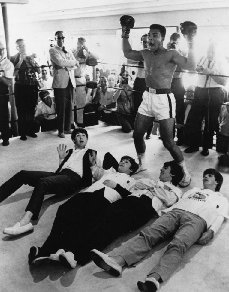 Cassius Clay doet alsof hij The Beatles tegen de grond heeft geslagen. Beeld Getty Images