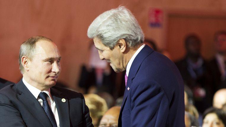 De Russische president Poetin (L) schudt de hand van John Kerry, minister van Buitenlandse Zaken voor de VS, na de speech van de Amerikaanse president Obama. Beeld ap