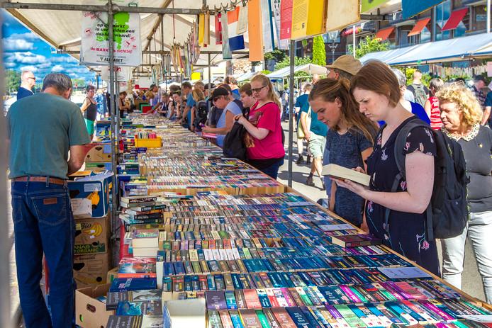 Bezoekers van de boekenmarkt speuren naar nieuwe aanwinsten voor in de boekenkast.