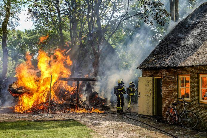 Schuur in brand naast woning met rieten dak in Made.