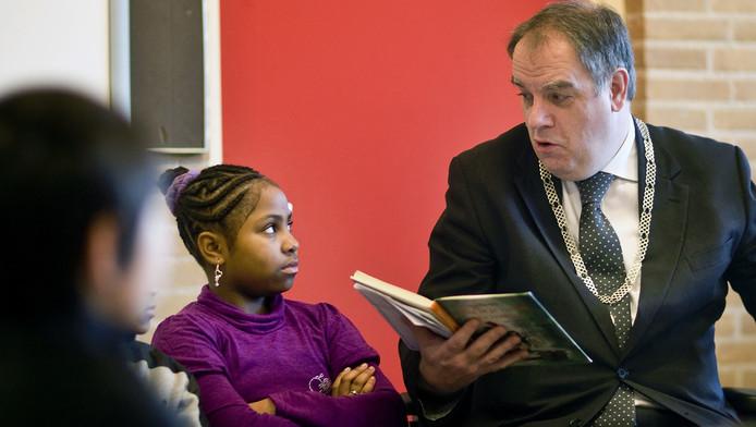 Bas Verkerk, burgemeester van Delft, leest voor op een basisschool.