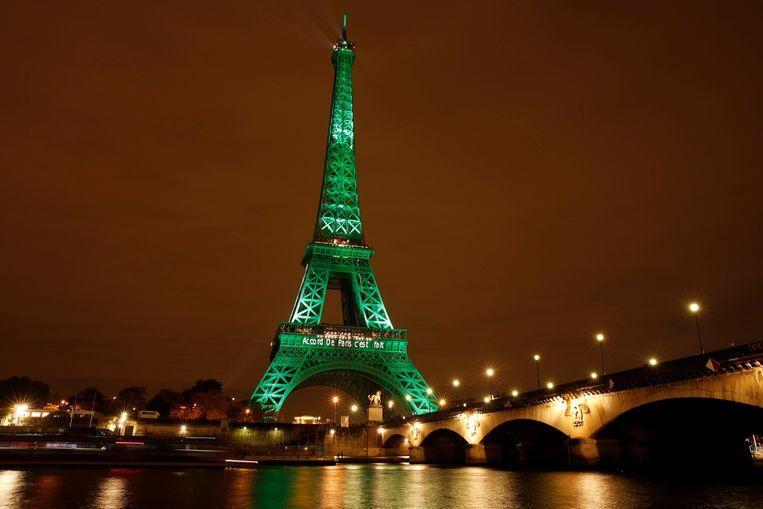Om het klimaatverdrag te vieren werd de Eiffeltoren groen uitgelicht. Beeld EPA