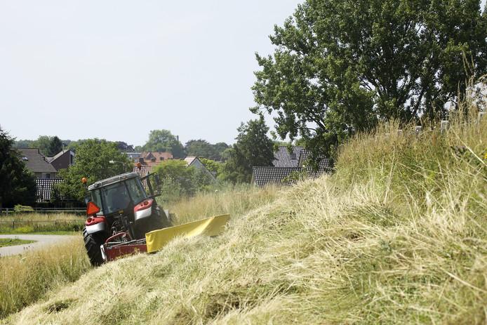 Maaien van grasland op de dijkhelling.