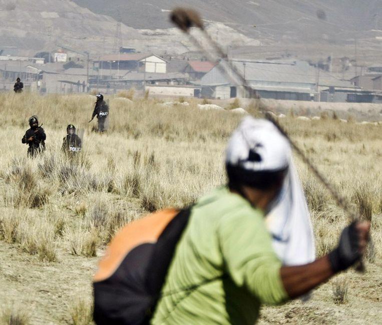 Een betoger in Peru gaat de politie te lijf met een katapult tijdens protesten tegen de mijnbouw. Beeld afp