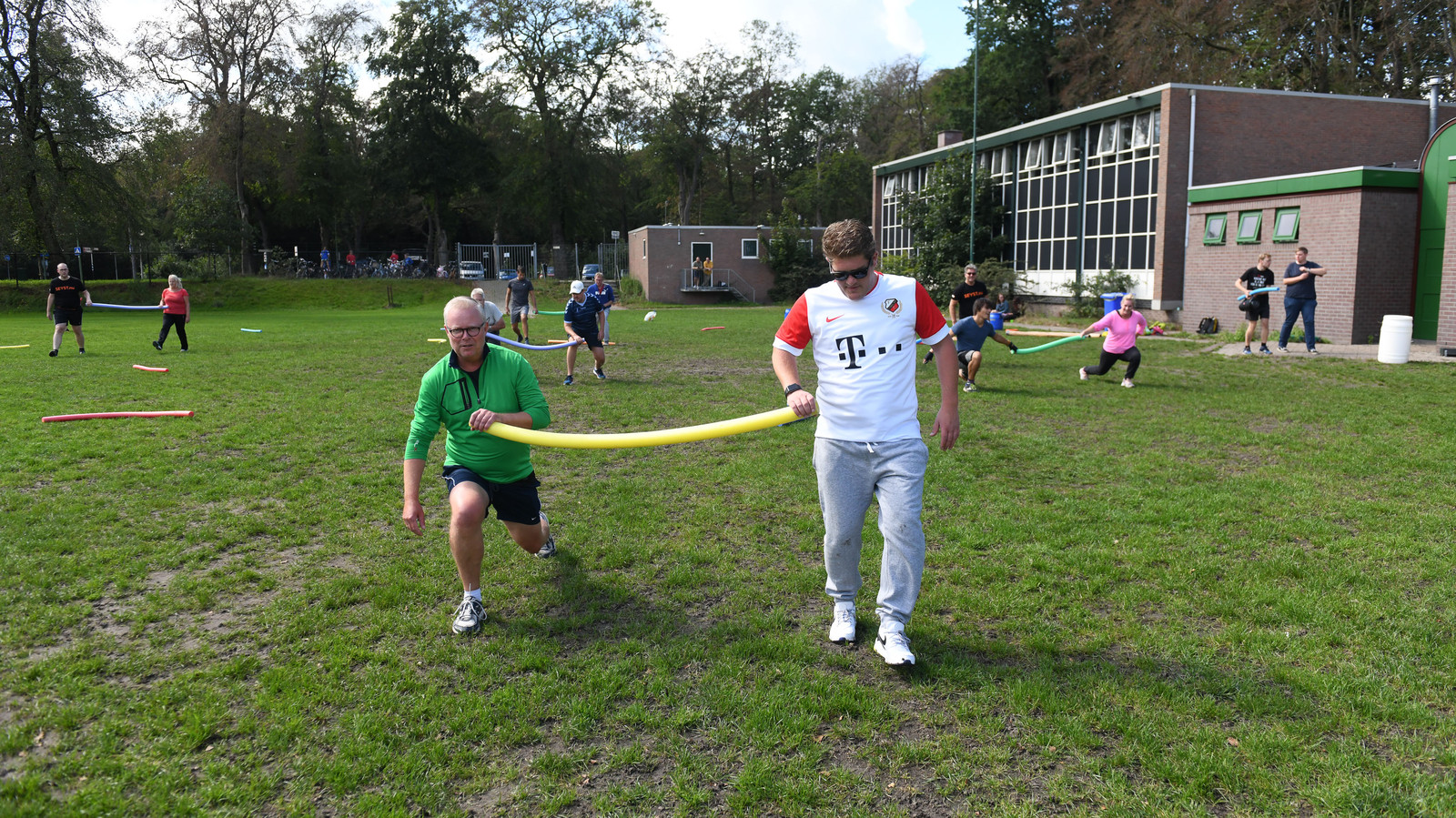 De raadsleden Walter van Dijk (VVD) en Vincent van Voorden (CDA) werken zich in het zweet op een sportveldje in Zeist.