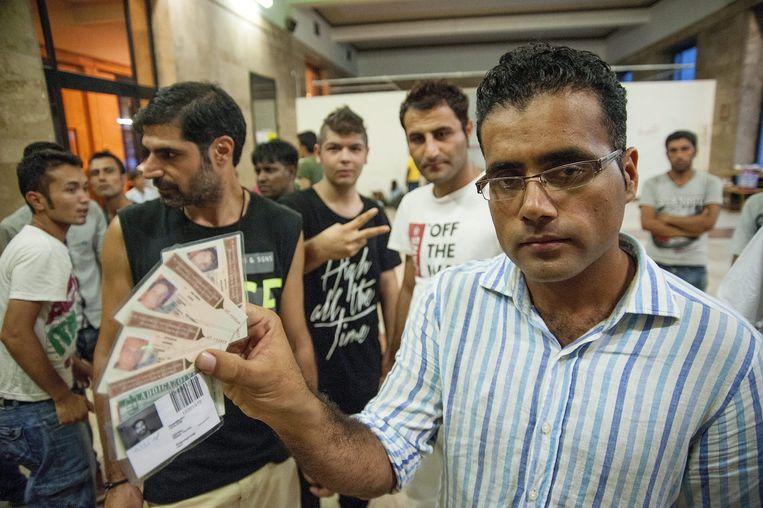 Een vluchtelingen laat documenten zien in het station in Boedapest. Beeld epa
