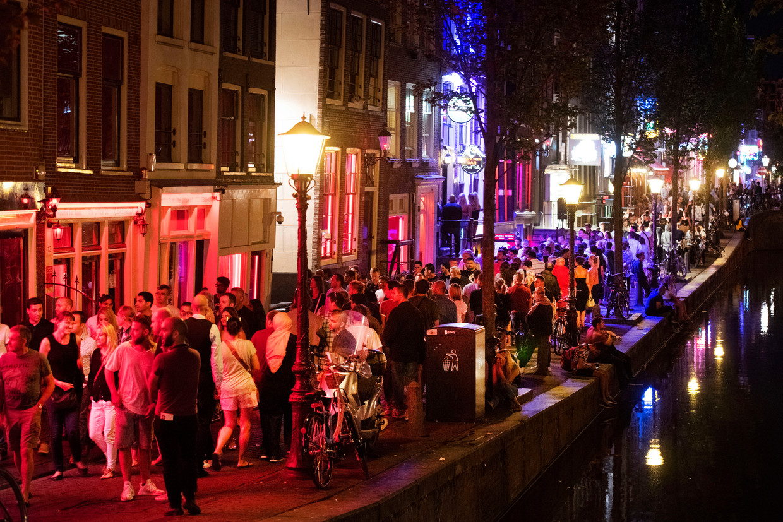 Op een zomerse avond trekken hordes toeristen langs de ramen op de Wallen.