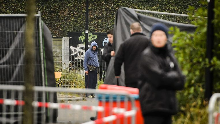 Een vluchteling kijkt hoe de ochtend na de bestorming extra hekken met plastic zeil worden neergezet voor sportcentrum Snellerpoort. Beeld anp