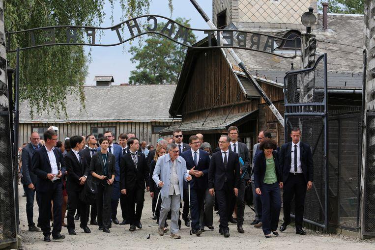 De Duitse Buitenlandminister Heiko Maas loopt samen met Holocaust-overlever Marian Turski onder de poort van vernietigingskamp Auschwitz door.