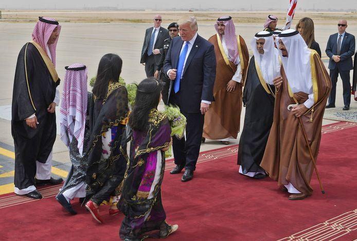 Kinderen met bloemen begroeten Donald Trump en de Saoedische koning Salman bin Abdulaziz al-Saud op het internationale vliegveld van Riyad.