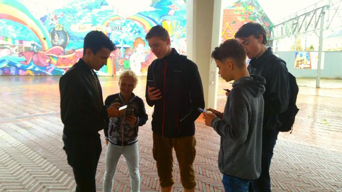 Tycho (l), Samim (rechts van Tycho) en Fay leggen uit hoe Pokemon Go werkt. Ook Yoeri Peters (rechts) en Rick van der Grient zijn op deze plek om te vechten voor de gym.