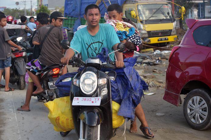 Inwoners van Palu met geplunderde goederen van winkelcentrum de Grand Mall.