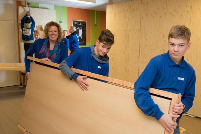Dominee Karolien Zwerver, die het initiatief nam voor de bijbelse escaperoom in de kelder van het Annahuis, helpt leerlingen vmbo 3 van het Carmel College Salland een handje bij het in elkaar puzzelen daarvan.