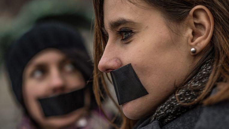 Tsjechische demonstranten hebben hun mond afgeplakt uit solidariteit met de Poolse media. Beeld epa