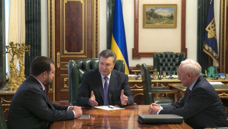 President Janoekovitsj (midden) met de gisteren opgestapte premier Azarov en vicepremier Arbuzov, op 21 januari in Kiev. Beeld null