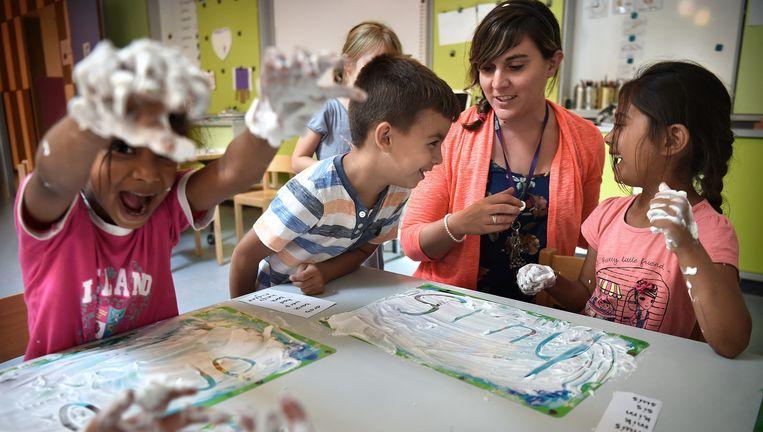 Kinderen uit groep 2 en 3 van basisschool De Klimroos in Utrecht schrijven woorden in scheerschuim. Beeld Marcel van den Bergh / de Volkskrant