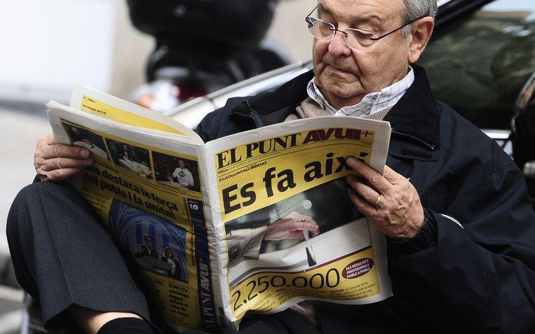 Een man leest de krant met de uitslag van de peiling op de voorpagina in Barcelona. Beeld ap