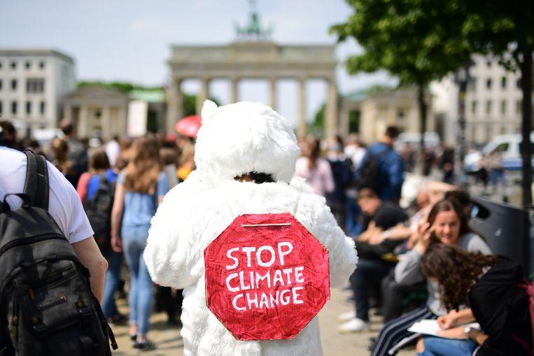Een demonstrant draagt een ijsberenpak met een bordje 'stop klimaatverandering' tijdens een klimaatmars in Berlijn.
