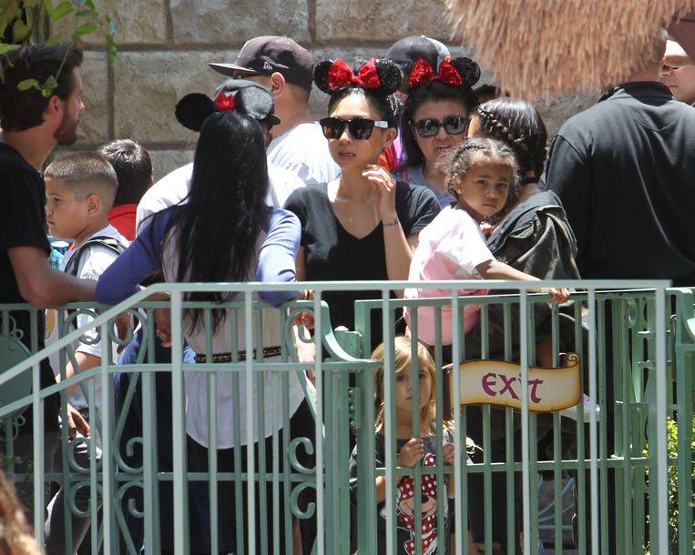 Kim Kardashian en dochter North in het Amerikaanse Disneyland, achter een groen hek.