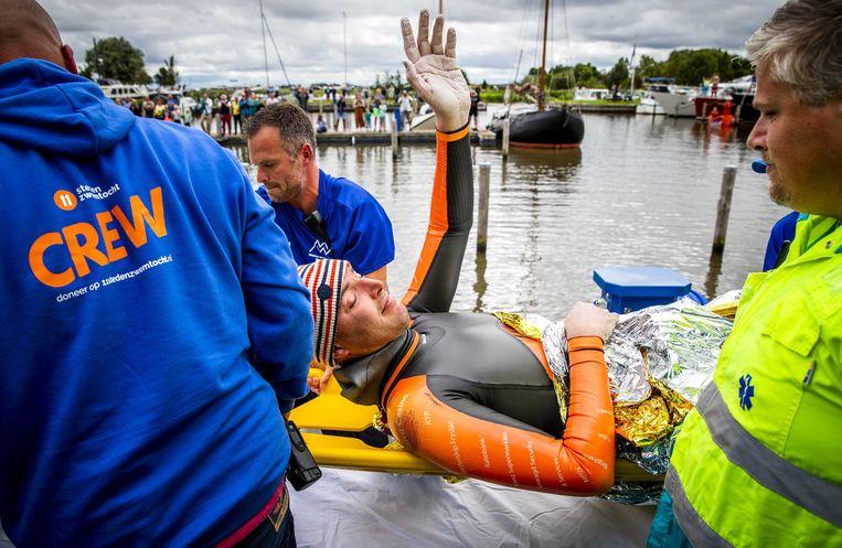 Maarten van der Weijden wordt na 163 kilometer zwemmen naar de ambulance gebracht. Beeld ANP