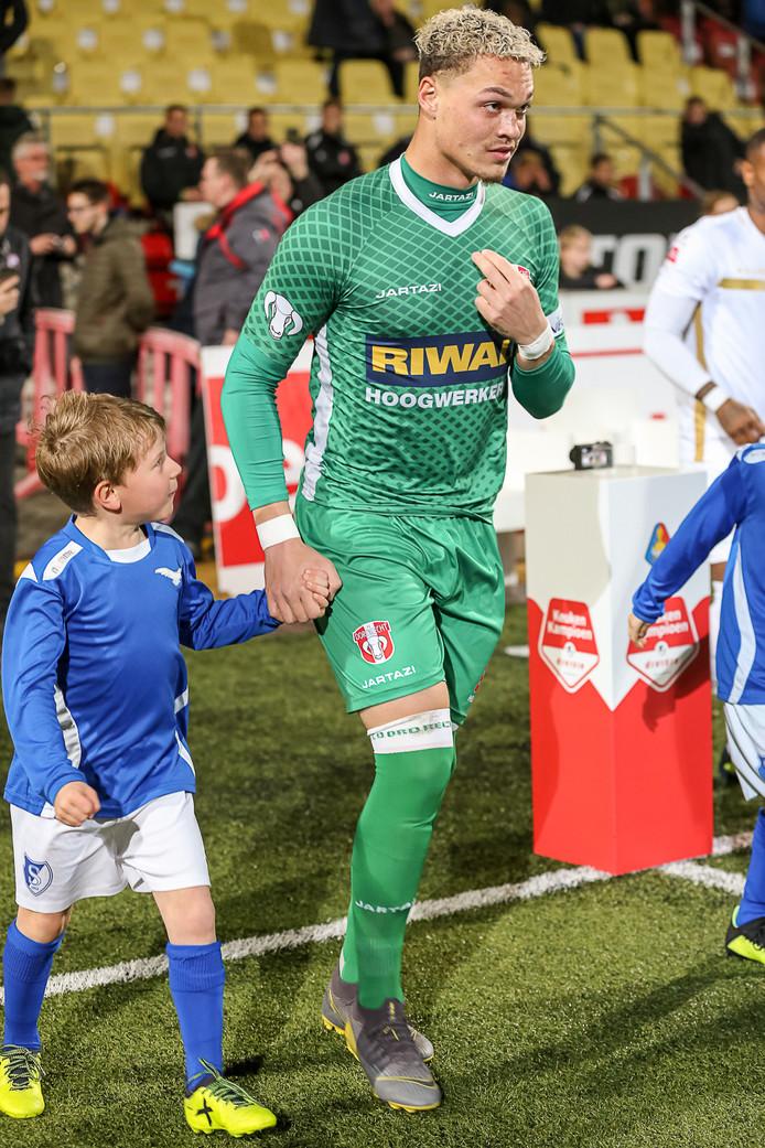 Joel Zwarts komt voorafgaand aan een wedstrijd het veld op met een pupil aan de hand.