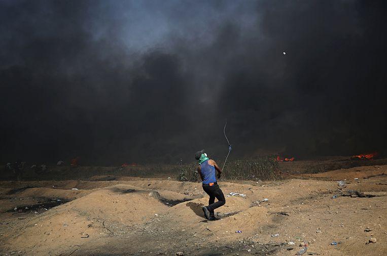 Een Palestijnse demonstrant werpt een steen. Beeld EPA