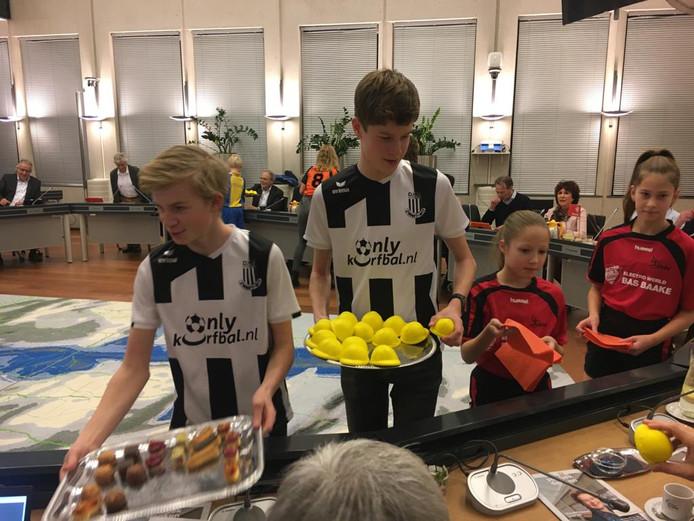 Jeugdleden van korfbalvereniging Zwart Wit, volleybalvereniging Devoc, handbalvereniging DHV en SV Delden delen een traktatie uit aan de gemeenteraad.