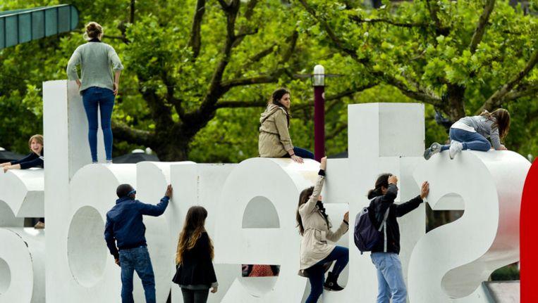 Toeristen bij het IAmsterdam logo op het Museumplein in Amsterdam. Beeld ANP