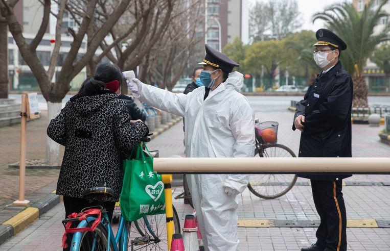 Een veiligheidsagent controleert de temperatuur van een inwoner van Wuhan, het epicentrum van de corona-uitbraak in China.