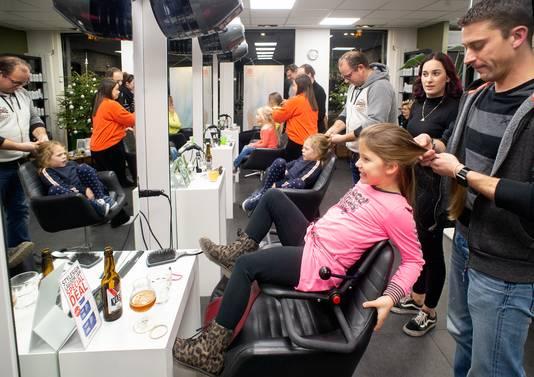 Vaders leren hun dochters' haren te vlechten bij kapsalon De Gruijter.
