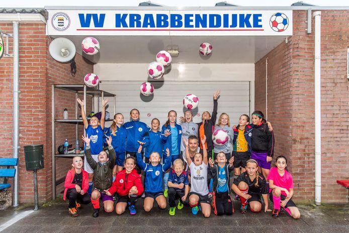 Bert de Rooij te midden van een groep voetballende meiden van Krabbendijke.