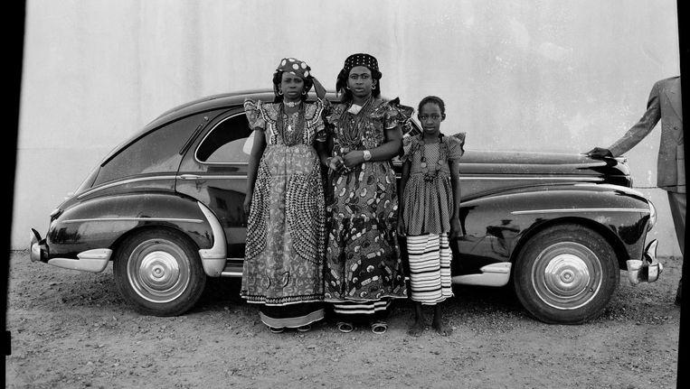 Drie vrouwen laten zich portretteren voor de Peugeot 203 van Seydou Keïta. In het spatbord is de reflectie van de fotograaf te zien Beeld Seydou Keïta